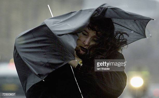 A pedestrian battles against strong gusty winds as she walks over Westminster Bridge January 8 2004 in London High winds and torrential rain has...