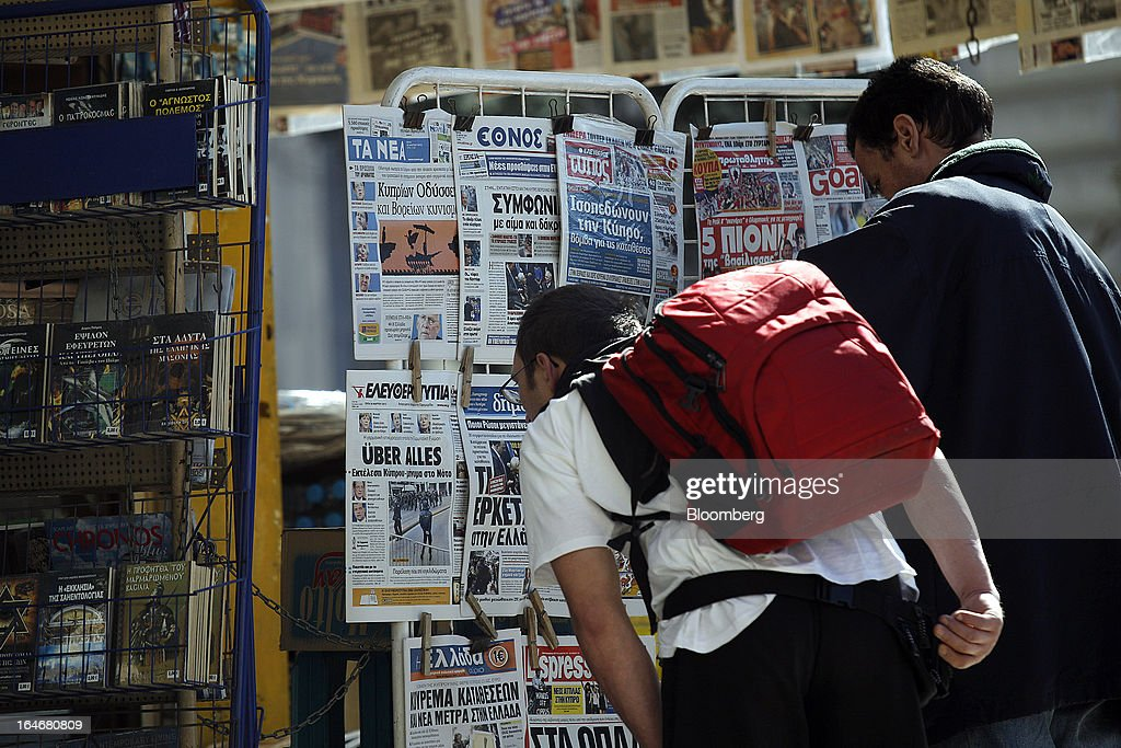 A pedestrian bends to look at the front pages of daily newspapers on display at a newstand in Athens, Greece, on Tuesday, March 26, 2013. Piraeus Bank SA acquires Greek units of Cypriot lenders for total cash consideration of EU524m, according to e-mailed statement from the Athens-based lender today. Photographer: Kostas Tsironis/Bloomberg via Getty Images