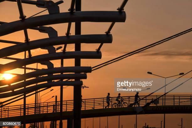 Pedestrian bridge across Mustafa Kemal boulevard at sunset in Izmir.