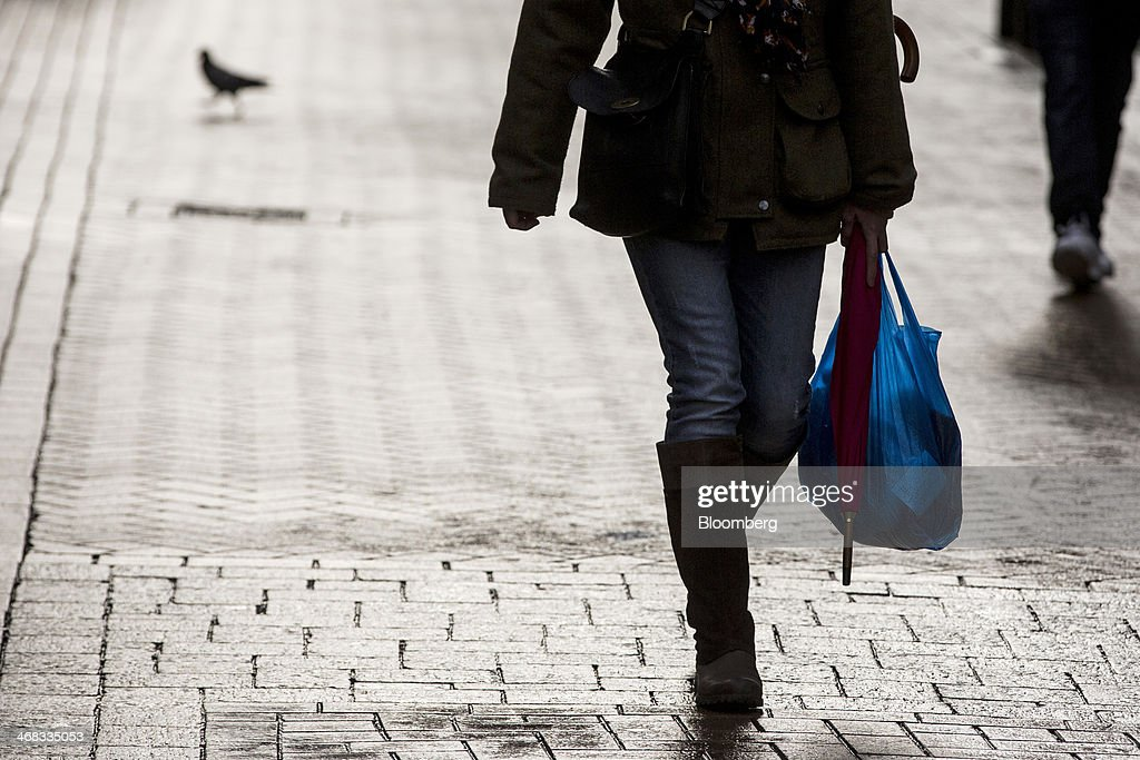A pedestrian carries a blue plastic carrier bag as she walks along a pedestrianized shopping street in Croydon, south London, U.K., on Monday, Feb. 10, 2014. Westfield Group, Australia's biggest mall operator, and Hammerson Plc won preliminary approval to rebuild the Whitgift Centre mall in south London as part of a project valued at about 1 billion pounds ($1.6 billion). Photographer: Jason Alden/Bloomberg via Getty Images
