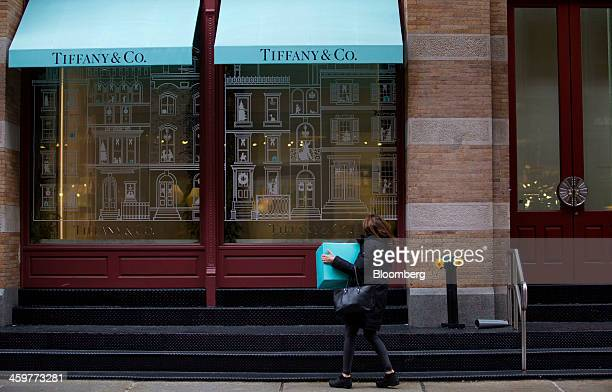A pedestrian carries a box while looking in the window of a Tiffany Co store in the Soho neighborhood of New York US on Monday Dec 30 2013 The...