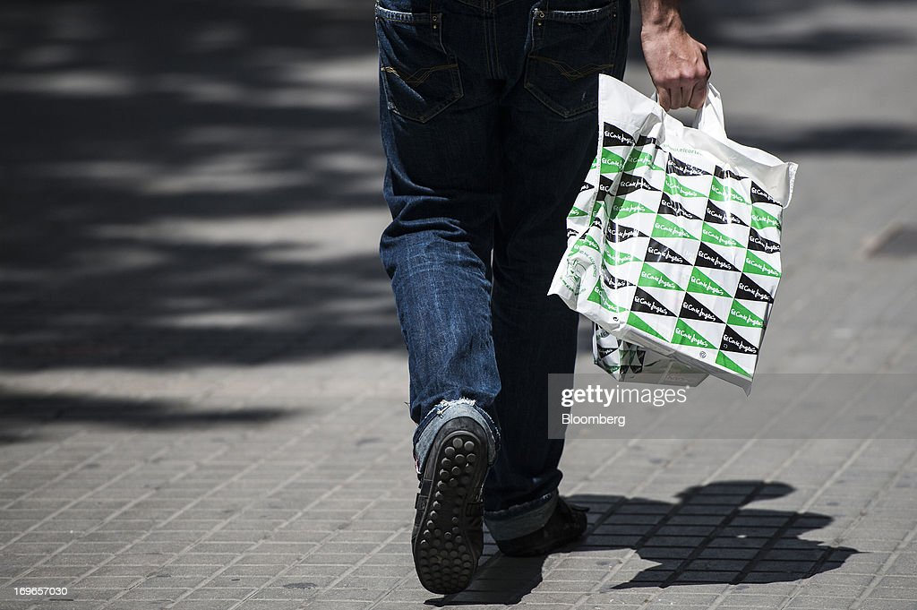 A pedestrian carries a branded shopping bag from the El Corte Ingles SA department store in Barcelona, Spain, on Thursday, May 30, 2013. Spain's recession eased in the first quarter as domestic demand stabilized while exports, which the government says will drive the recovery of the euro-area's fourth-largest economy, fell at the fastest pace in a year. Photographer: David Ramos/Bloomberg via Getty Images