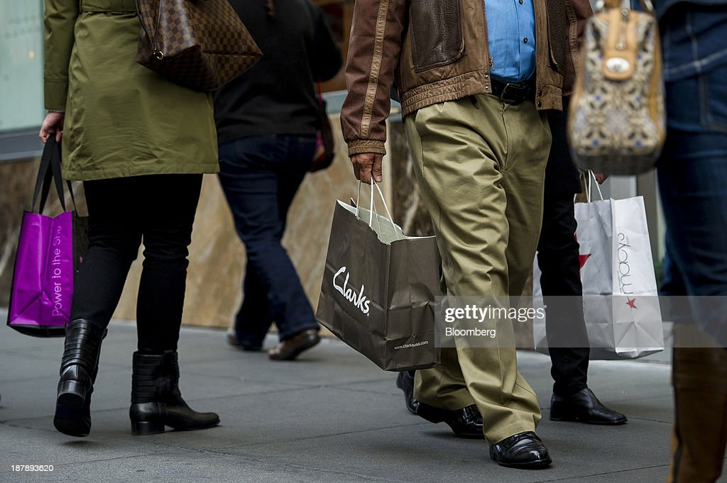 A pedestrian carries a Clarks shopping bag in San Francisco, California, U.S., on Monday, Nov. 11, 2013. The Bloomberg Consumer Comfort Index is scheduled to be released on Nov. 14. Photographer: David Paul Morris/Bloomberg via Getty Images