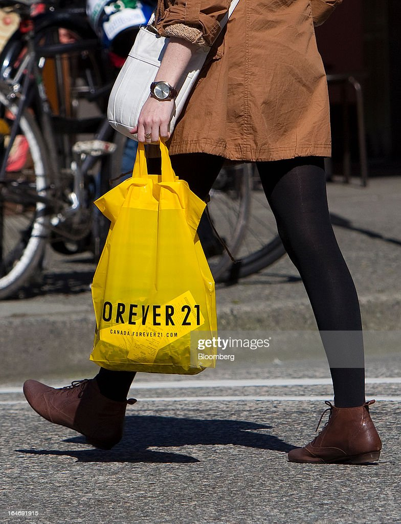 A pedestrian carries a Forever 21 Inc. shopping bag while walking on Robson Street in Vancouver, British Columbia, Canada, on Monday, March 25, 2013. Statistics Canada (STCA) is scheduled to release consumer price index data on March 27, 2013. Photographer: Ben Nelms/Bloomberg via Getty Images