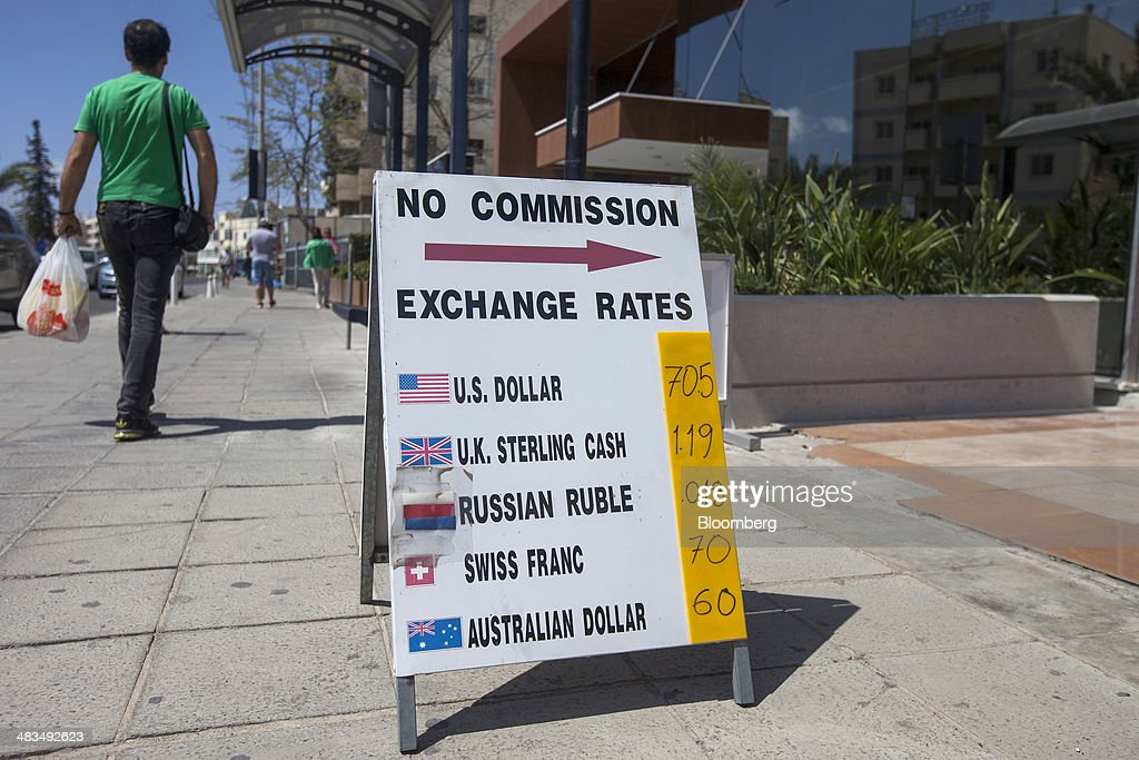 A pedestrian carries a grocery bag past a currency exchange sign advertising prices for Russian rubles on a sidewalk in Limassol, Cyprus, on Tuesday, April 8, 2014. Cyprus wants to shield financial flows with Russia, where it's the biggest foreign investor, as the U.S. and the European Union ratchet up sanctions in response to President Vladimir Putin's annexing Crimea from Ukraine. Photographer: Andrew Caballero-Reynolds/Bloomberg via Getty Images