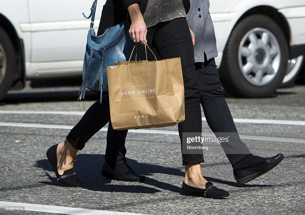 A pedestrian carries a Inditex SA Zara shopping bag while walking on Robson Street in Vancouver, British Columbia, Canada, on Monday, March 25, 2013. Statistics Canada (STCA) is scheduled to release consumer price index data on March 27, 2013. Photographer: Ben Nelms/Bloomberg via Getty Images