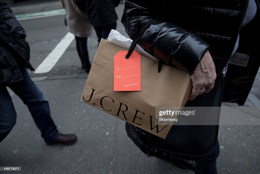 A pedestrian carries a J Crew Group Inc. shopping bag while walking in the Soho neighborhood of New York, U.S., on Monday, Dec. 30, 2013. The failure of United Parcel Service Inc. (UPS) and FedEx Corp. to deliver packages in time for Christmas has exposed the perils of retailers promising to get last-minute gifts to customers. Photographer: Jin Lee/Bloomberg via Getty Images