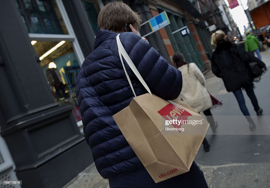 A pedestrian carries a Levi Strauss & Co. shopping bag while talking on a mobile phone in the Soho neighborhood of New York, U.S., on Monday, Dec. 30, 2013. The failure of United Parcel Service Inc. (UPS) and FedEx Corp. to deliver packages in time for Christmas has exposed the perils of retailers promising to get last-minute gifts to customers. Photographer: Jin Lee/Bloomberg via Getty Images