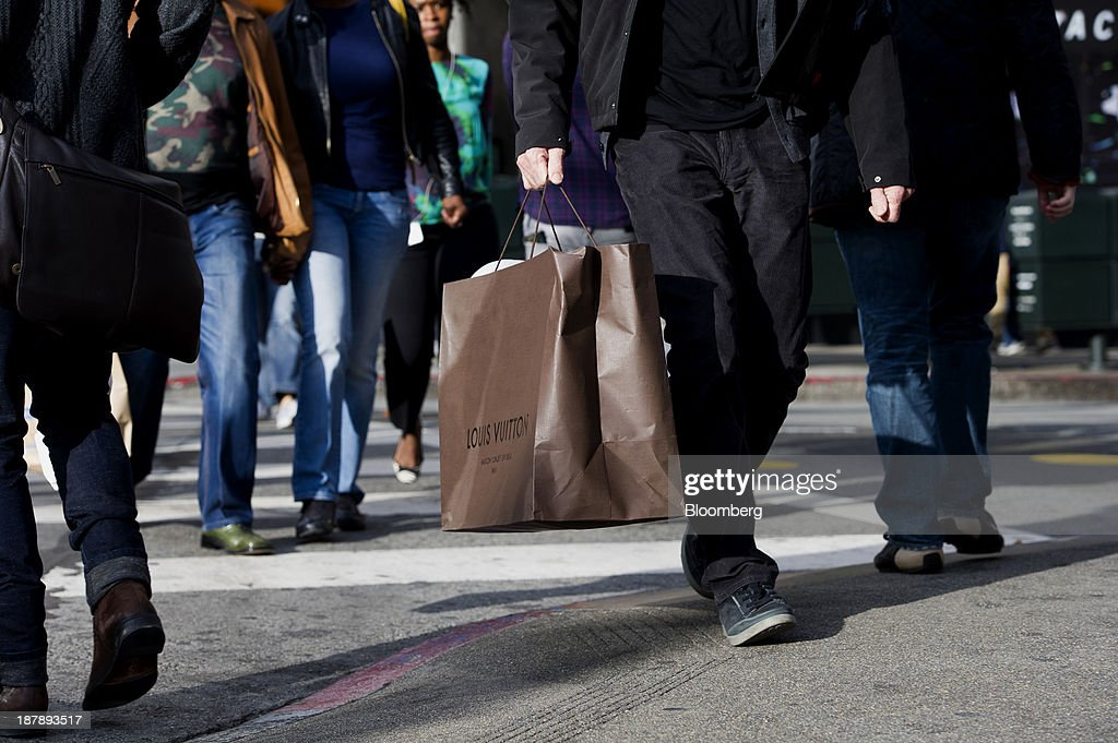 A pedestrian carries a LVMH Moet Hennessy Louis Vuitton SA shopping bag in San Francisco, California, U.S., on Monday, Nov. 11, 2013. The Bloomberg Consumer Comfort Index is scheduled to be released on Nov. 14. Photographer: David Paul Morris/Bloomberg via Getty Images
