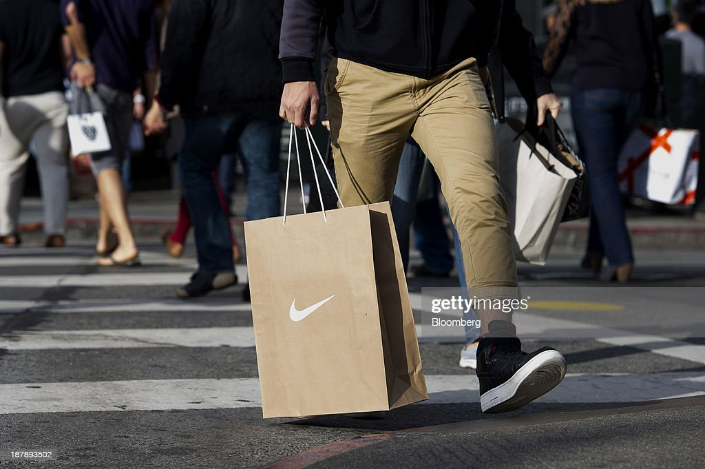A pedestrian carries a Nike Inc. shopping bag in San Francisco, California, U.S., on Monday, Nov. 11, 2013. The Bloomberg Consumer Comfort Index is scheduled to be released on Nov. 14. Photographer: David Paul Morris/Bloomberg via Getty Images