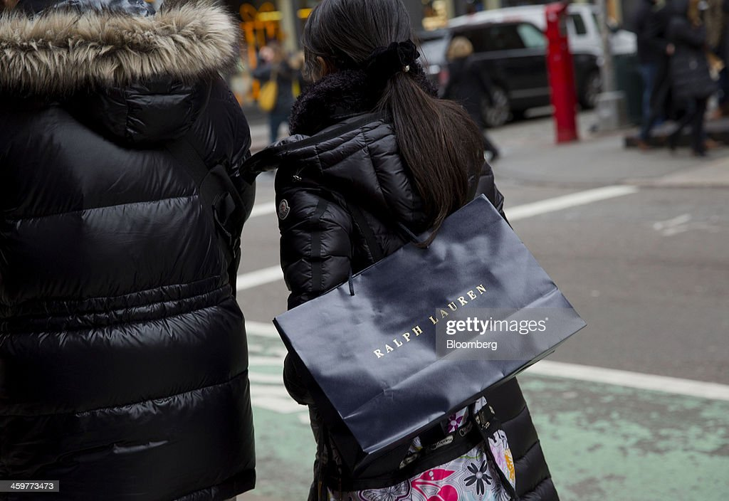 A pedestrian carries a Ralph Lauren Corp. shopping bag while walking in the Soho neighborhood of New York, U.S., on Monday, Dec. 30, 2013. The failure of United Parcel Service Inc. (UPS) and FedEx Corp. to deliver packages in time for Christmas has exposed the perils of retailers promising to get last-minute gifts to customers. Photographer: Jin Lee/Bloomberg via Getty Images