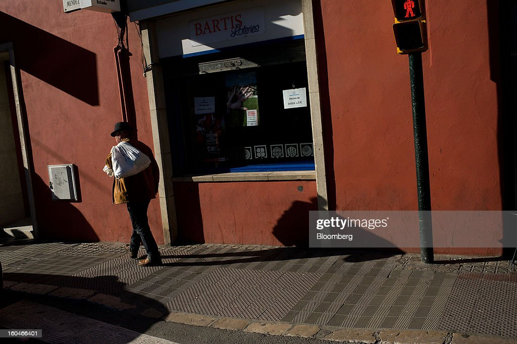 A pedestrian carries a sack along a street in Figueres, Spain, on Thursday, Jan. 31, 2013. Spain's recession deepened more than economists forecast in the fourth quarter as the government's struggle to rein in the euro region's second-largest budget deficit weighed on domestic demand. Photographer: David Ramos/Bloomberg via Getty Images