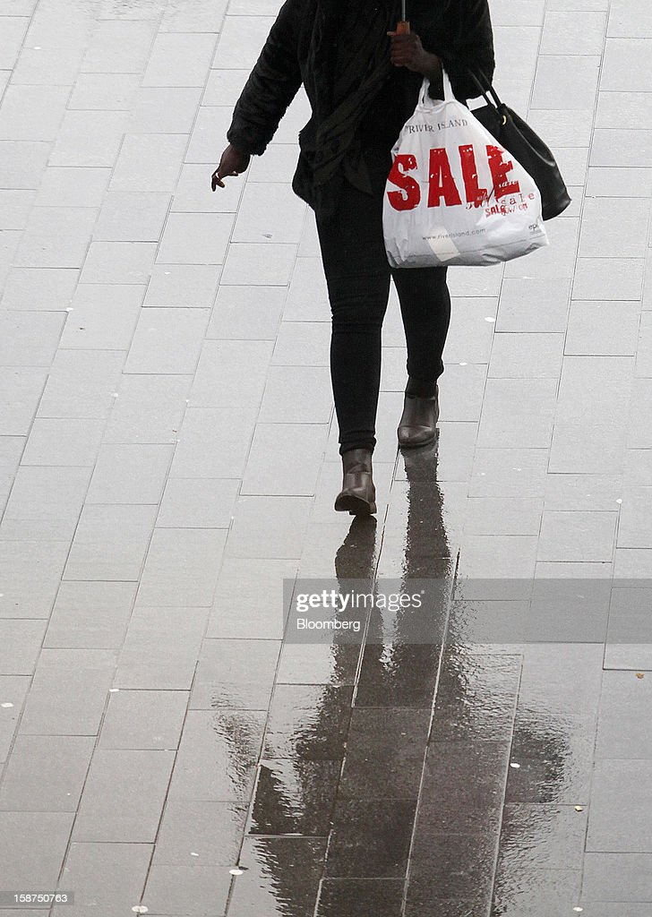 A pedestrian carries a 'Sale' branded River Island plastic shopping bag as she arrives at the Westfield Stratford City shopping mall in London, U.K., on Thursday, Dec. 27, 2012. Overall Christmas shopping in the U.K. was similar to last year, according to the British Retail Consortium. Photographer: Chris Ratcliffe/Bloomberg via Getty Images