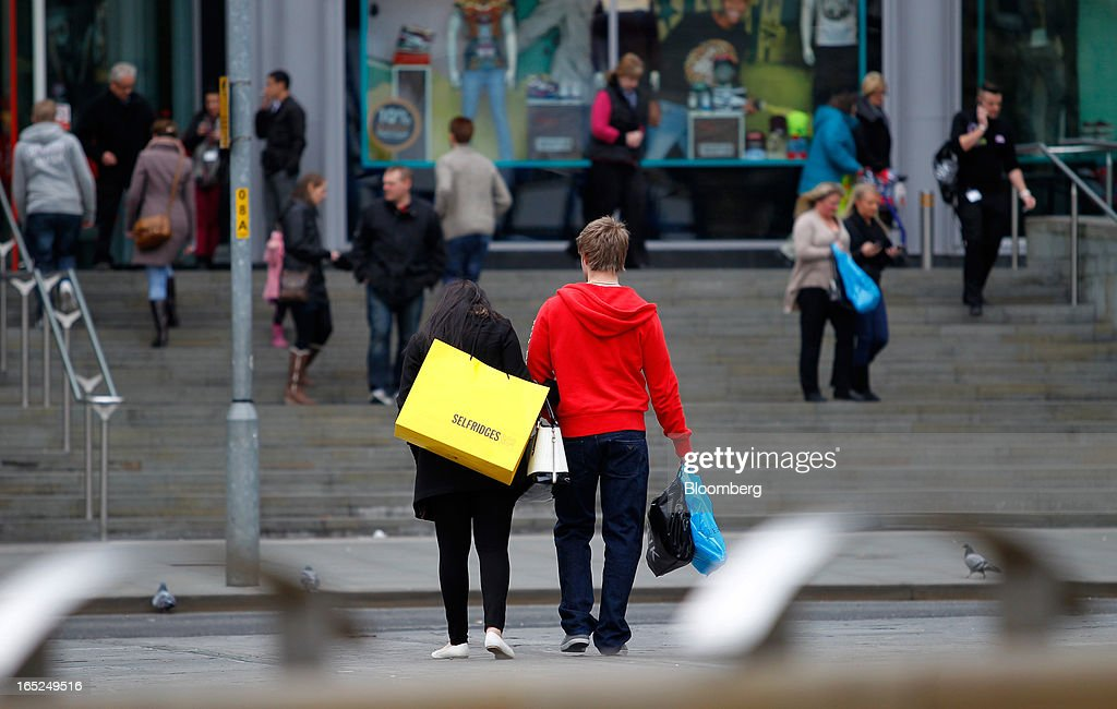 A pedestrian carries a Selfridges & Co.-branded shopping bag, center left, along a street in Manchester, U.K., on Monday, April 1, 2013. U.K. retail sales unexpectedly stagnated in March in a sign that consumer spending remains under pressure from higher energy bills and weak wage growth. Photographer: Paul Thomas/Bloomberg via Getty Images
