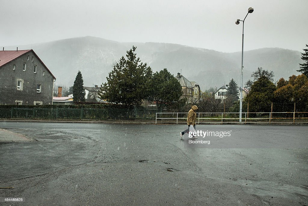 A pedestrian carries a shopping bag across an empty street in a town under threat from the expansion of nearby lignite mine excavations in Horni Jiretin, Czech Republic, on Friday, Dec. 6, 2013. The government may set up a joint company with Severni Energeticka that will seek lifting current environmental limits on lignite mining, Lidove Noviny reports, citing proposal submitted by Industry and Trade Ministry. Photographer: Bartek Sadowski/Bloomberg via Getty Images