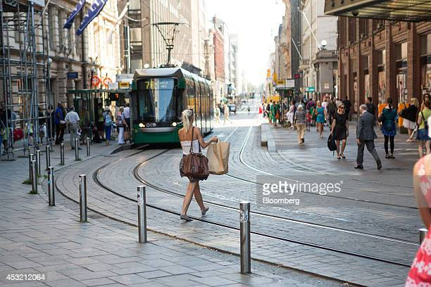 A pedestrian carries a shopping bag across tram tracks in a retail district of central Helsinki Finland on Tuesday Aug 5 2014 Compounding Finland's...