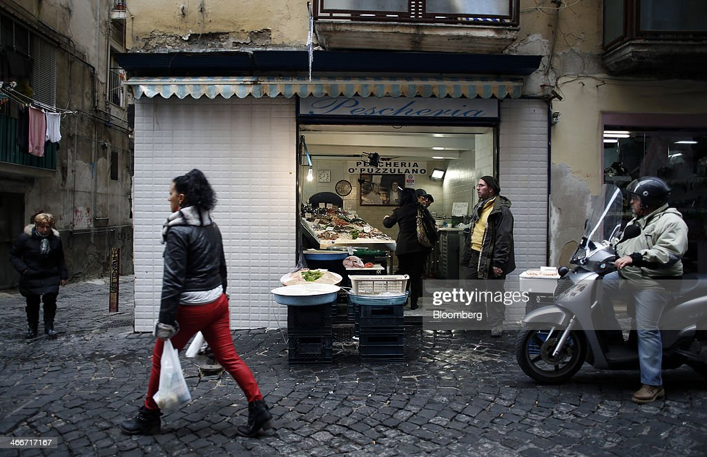 A pedestrian carries a shopping bag as she passes a fish shop in Naples, Italy, on Saturday, Feb. 1, 2014. In Naples, the local youth unemployment rate in 2012 was 53.6 percent compared to a national average of 35.3 percent. Photographer: Alessia Pierdomenico/Bloomberg via Getty Images