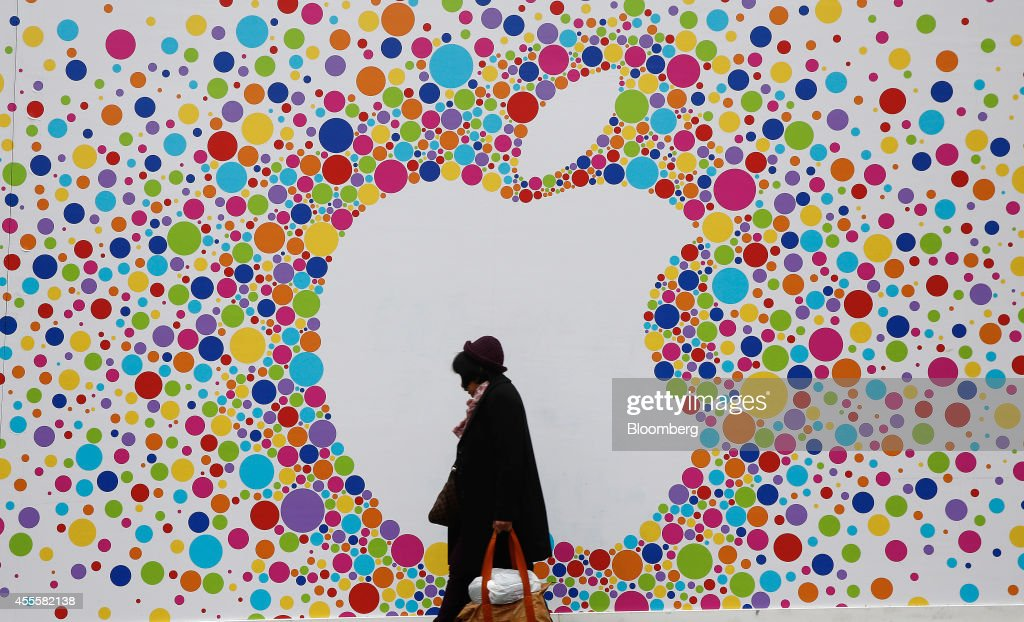 A pedestrian carries a shopping bag as she passes a giant Apple Inc. logo outside a new Apple store, still under development, on Princess Street in Edinburgh, U.K., on Wednesday, Sept. 17, 2014. Apple took orders for 4 million of its latest iPhone 6 smartphone in the first 24 hours, the Cupertino, California-based company said this week. Photographer: Simon Dawson/Bloomberg via Getty Images
