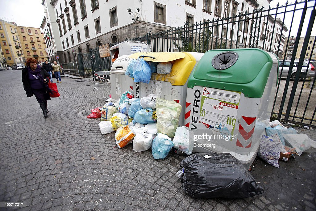 A pedestrian carries a shopping bag as she walks past overflowing garbage and recycling bins on a street in Naples, Italy, on Saturday, Feb. 1, 2014. In Naples, the local youth unemployment rate in 2012 was 53.6 percent compared to a national average of 35.3 percent. Photographer: Alessia Pierdomenico/Bloomberg via Getty Images