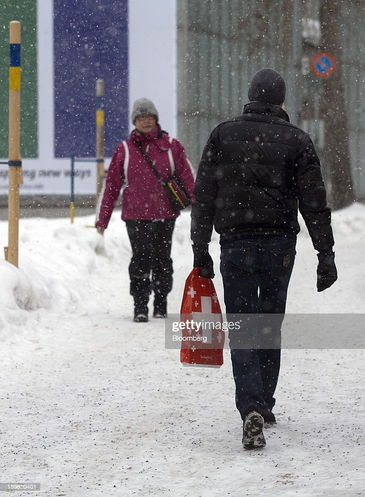 A pedestrian carries a shopping bag branded with the Swiss national logo, right, as he walks through the snow in Davos, Switzerland, on Monday, January 21, 2013. This week the business elite gathers in the Swiss Alps for the 43rd annual meeting of the World Economic Forum in Davos, the five day event runs from Jan. 23-27. Photographer: Simon Dawson/Bloomberg via Getty Images