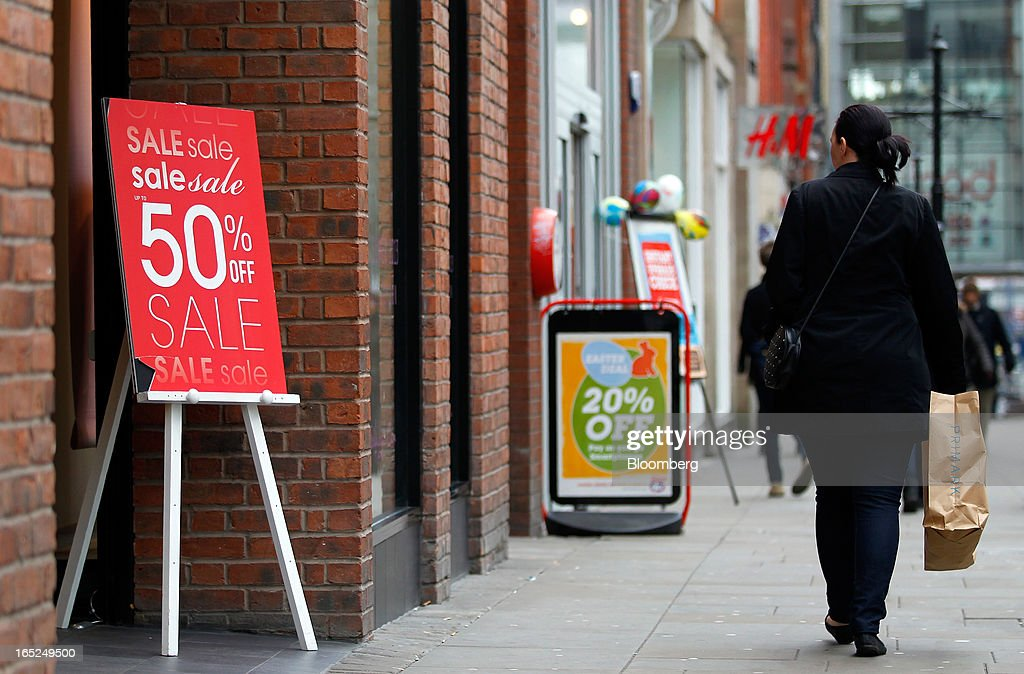 A pedestrian carries a shopping bag past a sign advertising a sale outside a Miss Selfridge fashion store in Manchester, U.K., on Monday, April 1, 2013. U.K. retail sales unexpectedly stagnated in March in a sign that consumer spending remains under pressure from higher energy bills and weak wage growth. Photographer: Paul Thomas/Bloomberg via Getty Images