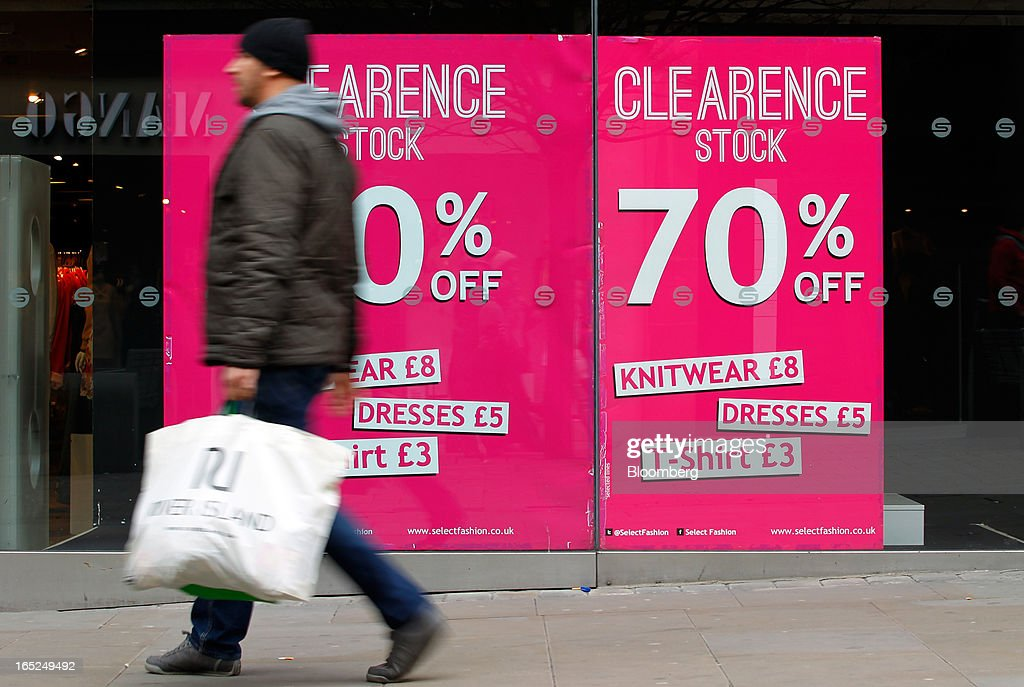 A pedestrian carries a shopping bag past a window advertisement for a stock clearance sale at a Select store in Manchester, U.K., on Monday, April 1, 2013. U.K. retail sales unexpectedly stagnated in March in a sign that consumer spending remains under pressure from higher energy bills and weak wage growth. Photographer: Paul Thomas/Bloomberg via Getty Images