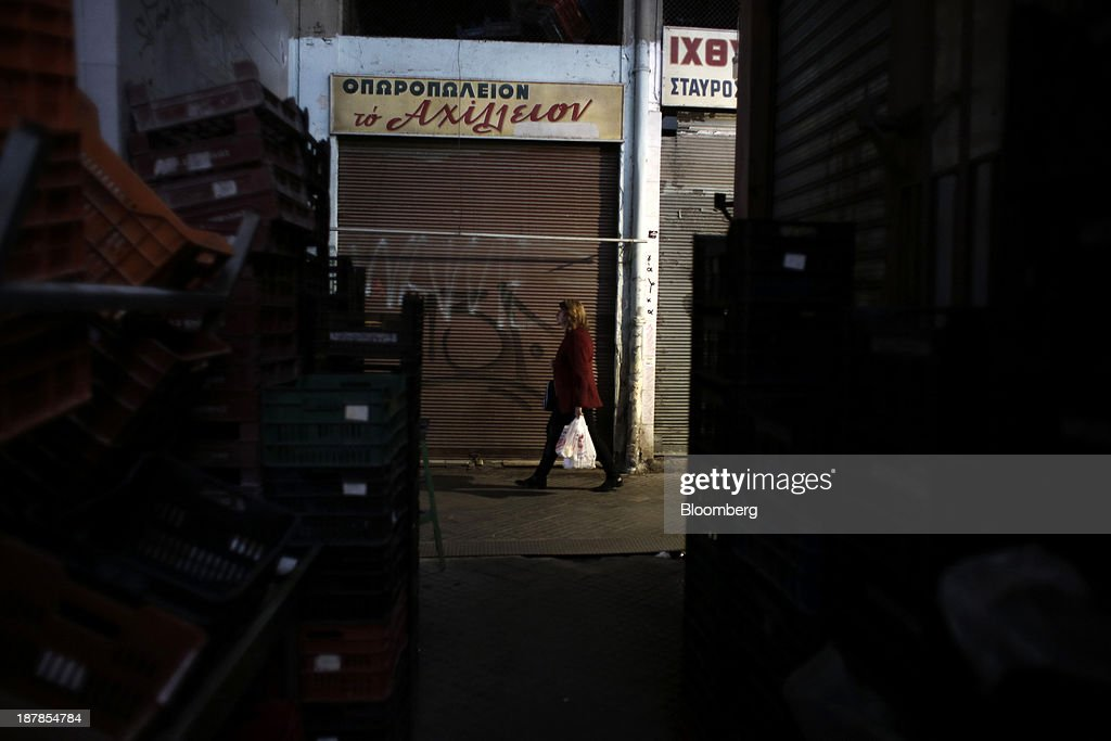 A pedestrian carries a shopping bag past closed down stores in the Modiano district market in Thessaloniki, Greece, on Wednesday, Nov. 13, 2013. Greece 'is following a fiscal adjustment program that aims to make the country's public finances sustainable on a permanent basis,' Finance Minister Yannis Stournaras told lawmakers during the debate, after holding talks with the troika earlier in the week. Photographer: Konstantinos Tsakalidis/Bloomberg via Getty Images