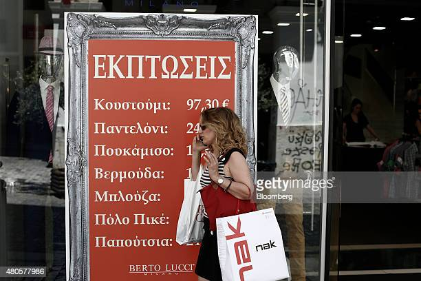 A pedestrian carries a shopping bag past the window of a fashion store advertising sales discounts in the summer sales in Athens Greece on Monday...