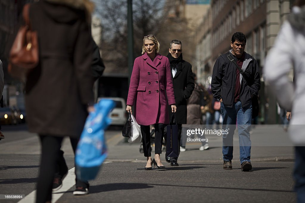 A pedestrian carries a shopping bag while crossing the street in New York, U.S., on Thursday, April 4, 2013. Confidence among U.S. consumers stabilized last week, stemming a pullback in sentiment that had threatened to check recent gains in spending. Photographer: Victor J. Blue/Bloomberg via Getty Images