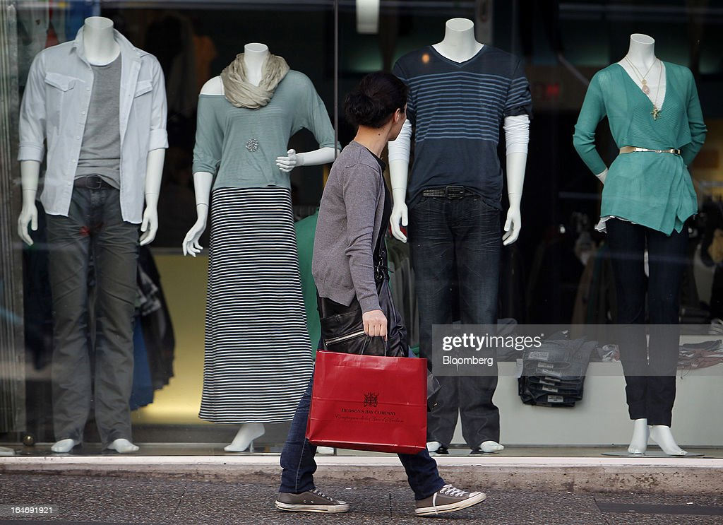 A pedestrian carries a shopping bag while walking viewing mannequins in a store on Robson St. in Vancouver, British Columbia, Canada, on Monday, March 25, 2013. Statistics Canada (STCA) is scheduled to release consumer price index data on March 27, 2013. Photographer: Ben Nelms/Bloomberg via Getty Images