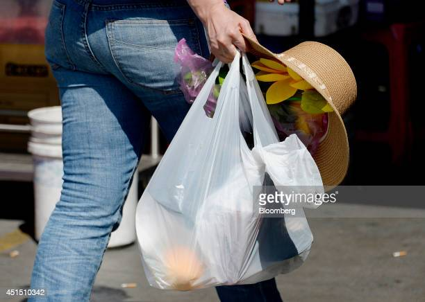 A pedestrian carries a singleuse plastic bag while shopping in the Chinatown section of Los Angeles California US on Tuesday June 24 2014 California...