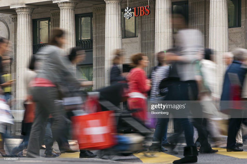 A pedestrian carries a Swiss flag-branded bag across a road in front of a UBS AG bank branch in Lausanne, Switzerland, on Monday, April 30, 2012. UBS AG will post first quarter earnings earnings on May 2. Photographer: Valentin Flauraud/Bloomberg via Getty Images