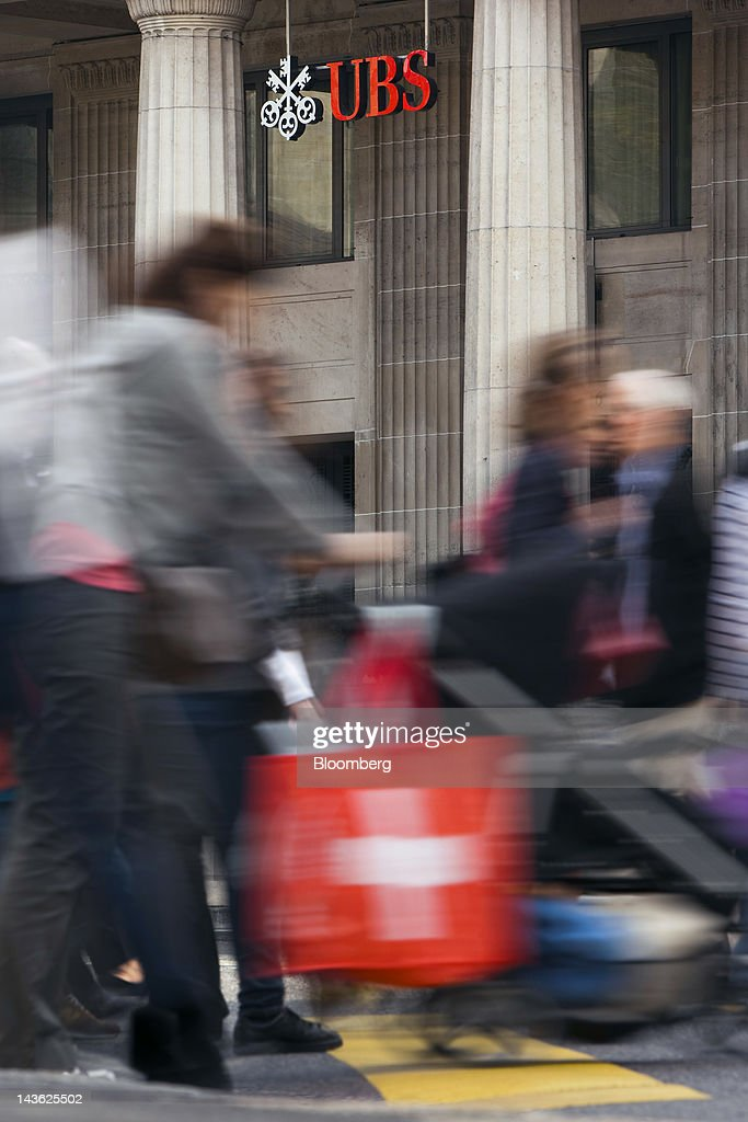 A pedestrian carries a Swiss flag-branded bag as they cross a road in front of a UBS AG bank branch in Lausanne, Switzerland, on Monday, April 30, 2012. UBS AG will post first quarter earnings earnings on May 2. Photographer: Valentin Flauraud/Bloomberg via Getty Images