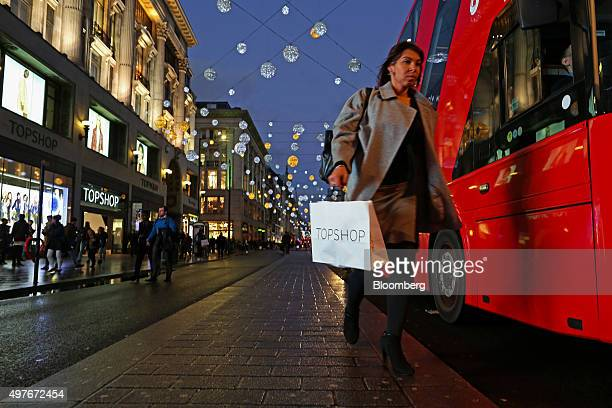 A pedestrian carries a Topshop shopping bag as she walks down Oxford Street beneath suspended Christmas lights and decorations in London UK on...
