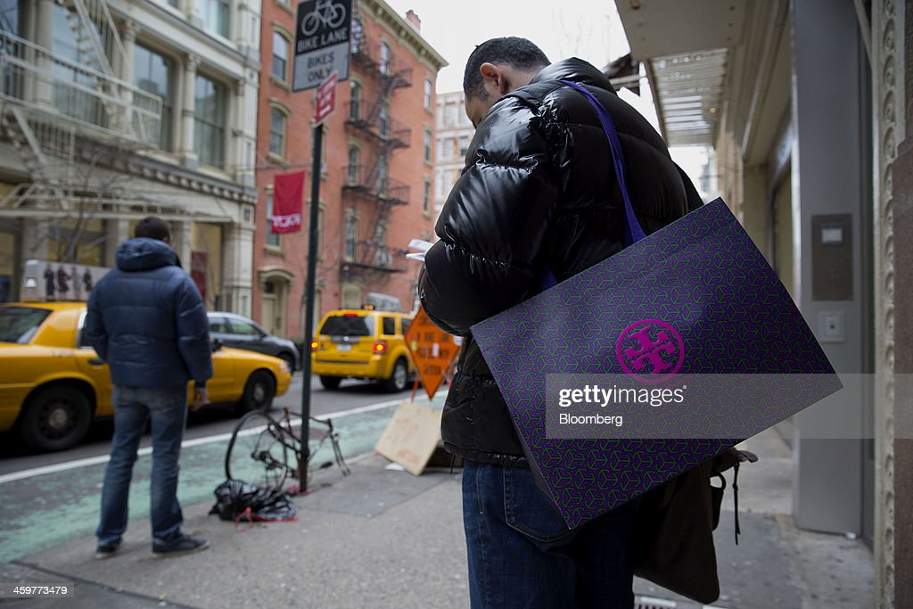 A pedestrian carries a Tory Burch LLC shopping bag in the Soho neighborhood of New York, U.S., on Monday, Dec. 30, 2013. The failure of United Parcel Service Inc. (UPS) and FedEx Corp. to deliver packages in time for Christmas has exposed the perils of retailers promising to get last-minute gifts to customers. Photographer: Jin Lee/Bloomberg via Getty Images