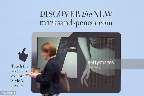 A pedestrian carries a tray of coffee cups past a 'touch screen' display advertising Marks Spencer's website outside the company's retail store...