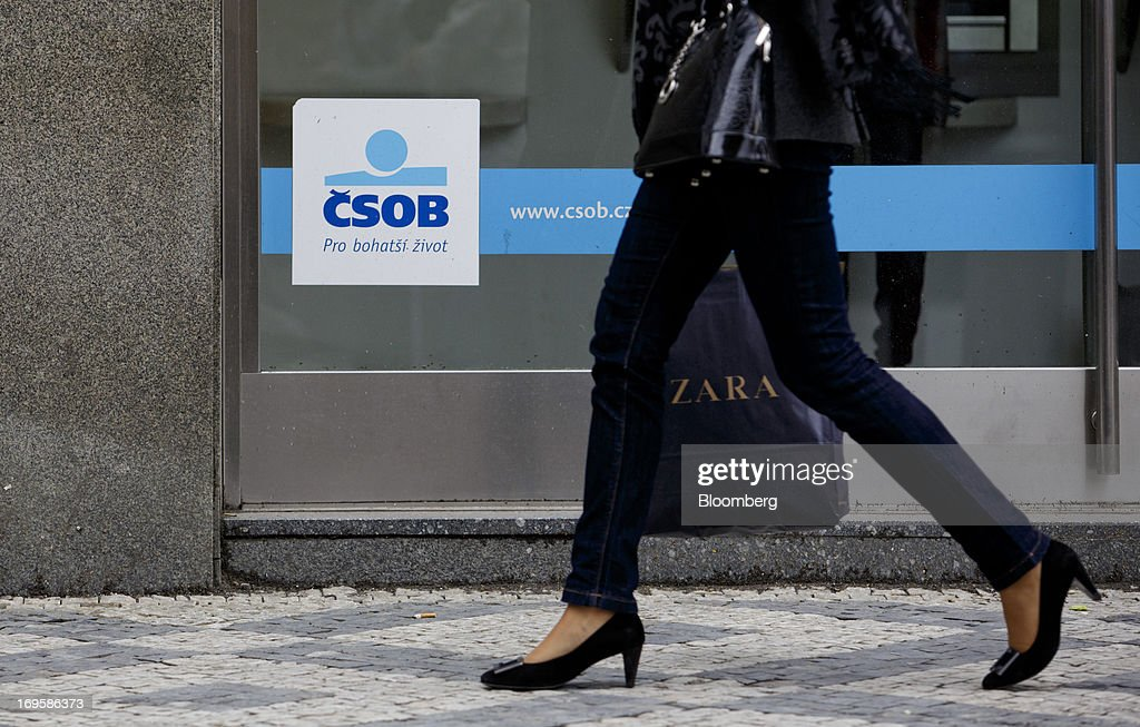 A pedestrian carries a Zara shopping bag past a branch of CSOB AB, the Czech unit of KBC Groep NV bank, in Prague, Czech Republic, on Monday, May 27, 2013. Czech policy makers are in uncharted territory as they debate whether the first koruna sales in a decade are needed to meet their inflation target as the economy has shrunk for five quarters, the longest contraction since at least 1996. Photographer: Martin Divisek/Bloomberg via Getty Images
