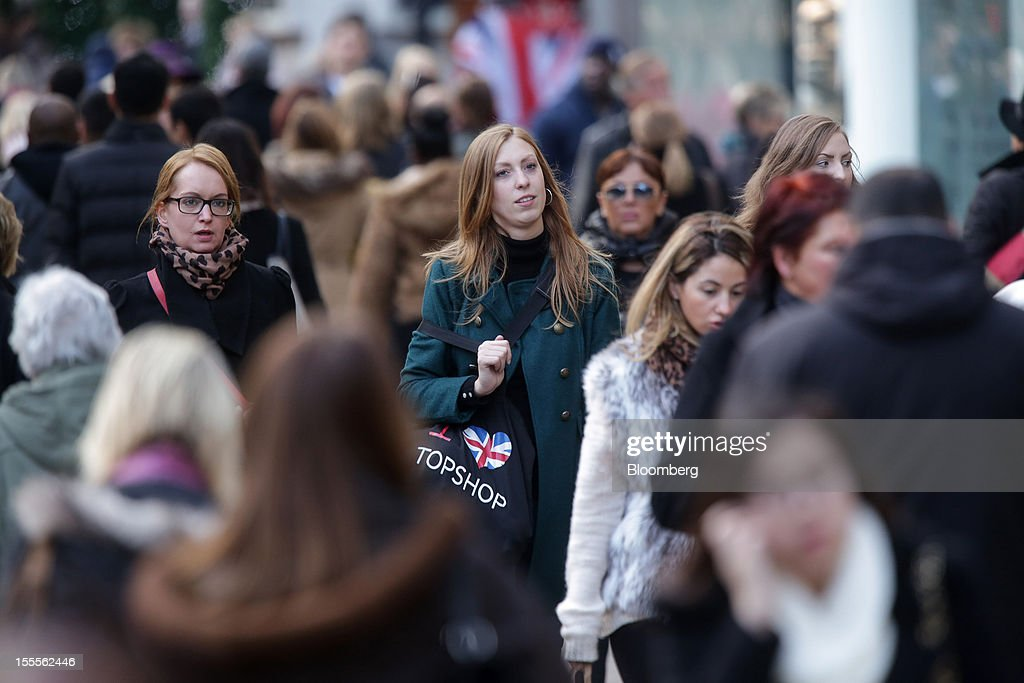 A pedestrian carries an 'I Love Topshop' shopping bags along Oxford Street in central London, U.K., on Monday, Nov. 5, 2012. Britain exited a double-dip recession in the third quarter with the strongest growth in five years as Olympic ticket sales and a surge in services helped boost the rebound. Photographer: Jason Alden/Bloomberg via Getty Images
