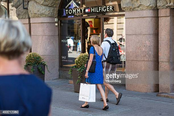 A pedestrian carries an Iittala AB branded shopping bag past a Tommy Hilfiger Group fashion store in central Helsinki Finland on Tuesday Aug 5 2014...