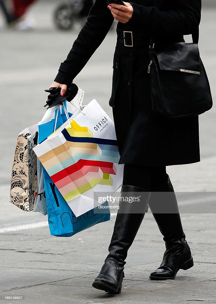 A pedestrian carries an Office-branded shopping bag in Manchester, U.K., on Monday, April 1, 2013. U.K. retail sales unexpectedly stagnated in March in a sign that consumer spending remains under pressure from higher energy bills and weak wage growth. Photographer: Paul Thomas/Bloomberg via Getty Images