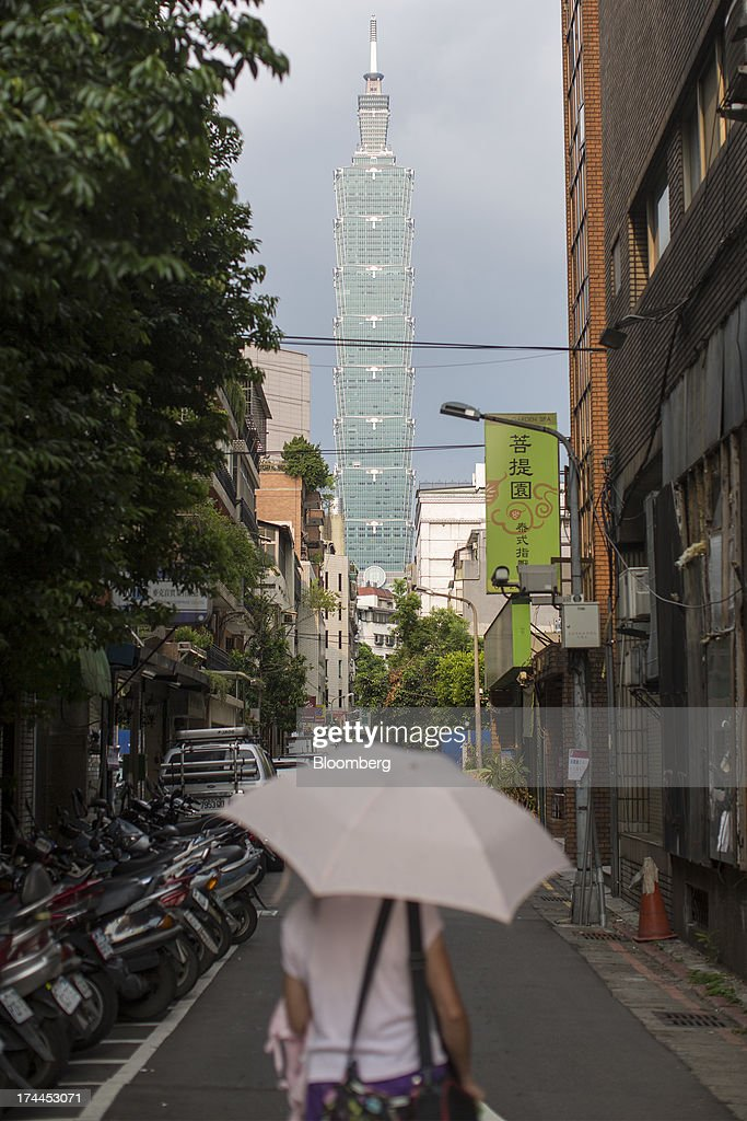 A pedestrian carries an umbrella as she walks down a street as the Taipei 101 building stands in the background in Taipei, Taiwan, on Wednesday, July 24, 2013. Taiwan President Ma Ying-jeou ruled out driving down the Taiwan dollar to boost exports following the currencys rally against the yen and said the government still aims for growth of at least 2 percent this year. Photographer: Jerome Favre/Bloomberg via Getty Images