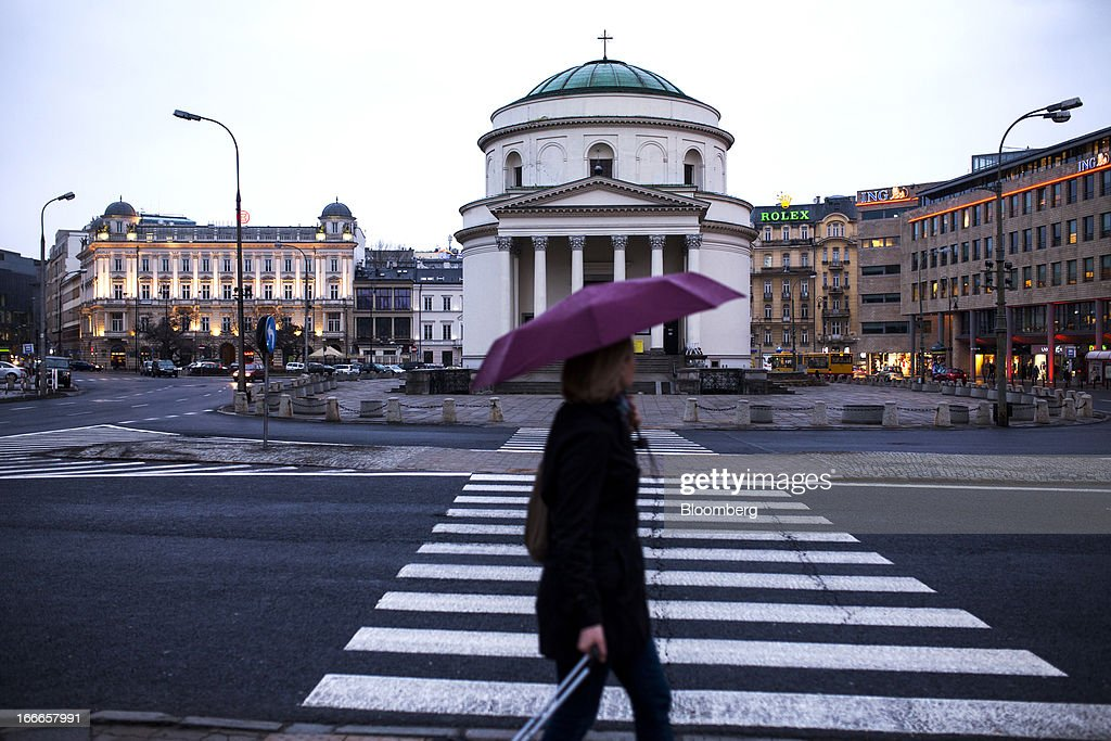 A pedestrian carries an umbrella past a road crossing in central Warsaw, Poland, on Thursday, April 11, 2013. Poland's central bank kept interest rates unchanged at a record-low 3.25 percent yesterday. Photographer: Bartek Sadowski/Bloomerg