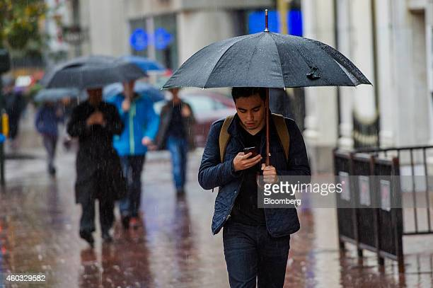 A pedestrian carries an umbrella while checking mobile phone in the rain on Market Street in San Francisco California US on Thursday Dec 11 2014 San...