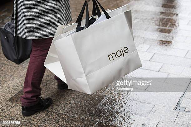 A pedestrian carries branded shopping bags from a Maje luxury clothing store operated by SMCP Group in Toulouse France on Wednesday Feb 10 2016...