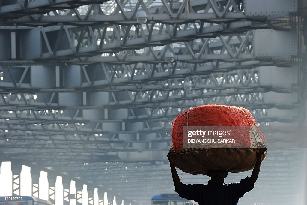 A pedestrian carries goods over his head as he makes his way across the Howrah bridge during a two-day strike opposing the current UPA governments economic policies in Kolkata on February 20, 2013. Millions of India's workers walked off their jobs in a two-day nationwide strike called by trade unions to protest at the 'anti-labour' policies of the embattled government. Financial services and transport were hit by the strike called by 11 major workers' groups to protest at a series of pro-market economic reforms announced by the government last year, as well as high inflation and rising fuel prices. AFP PHOTO/Dibyangshu SARKAR