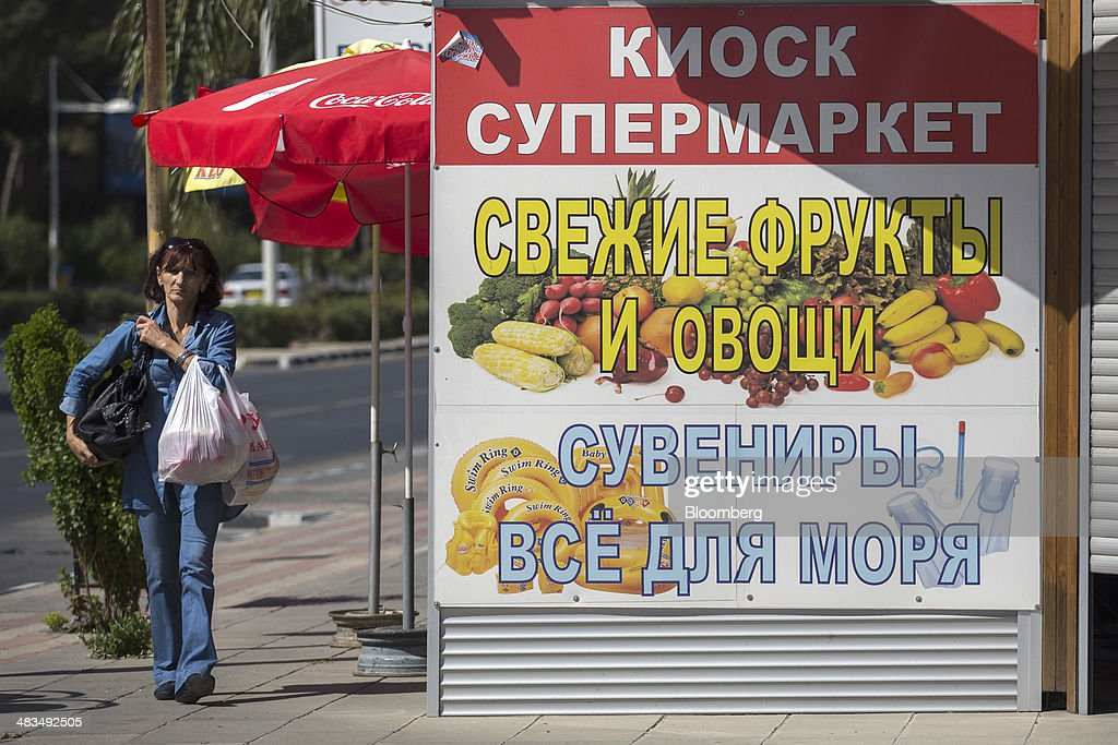 A pedestrian carries grocery bags past a supermarket advertisement written in Russian cyrillic script in Limassol, Cyprus, on Tuesday, April 8, 2014. Cyprus wants to shield financial flows with Russia, where it's the biggest foreign investor, as the U.S. and the European Union ratchet up sanctions in response to President Vladimir Putin's annexing Crimea from Ukraine. Photographer: Andrew Caballero-Reynolds/Bloomberg via Getty Images