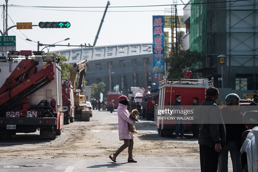 A pedestrian (C) carries her dog as she walks past the site of a collapsed building in the southern Taiwanese city of Tainan on February 7, 2016, following a strong 6.4-magnitude earthquake that struck early on February 6. Rescuers raced on February 7 to free more than 120 people buried under the rubble of an apartment complex felled by an earthquake in southern Taiwan that left 24 confirmed dead, as an investigation began into the collapse. AFP PHOTO / ANTHONY WALLACE / AFP / ANTHONY WALLACE