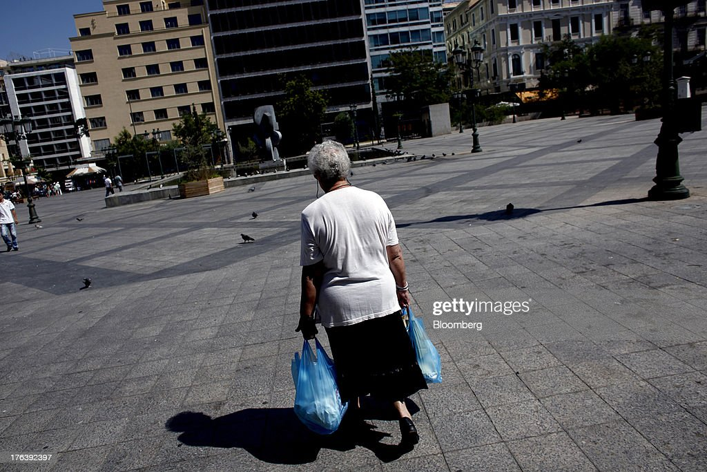 A pedestrian carries her shopping in plastic carrier bags across a square in Athens, Greece, on Saturday, Aug. 10, 2013. Greece's economy contracted for a 20th quarter, extending an economic slump that has left more than six in 10 young Greeks out of work. Photographer: Angelos Tzortzinis/Bloomberg via Getty Images