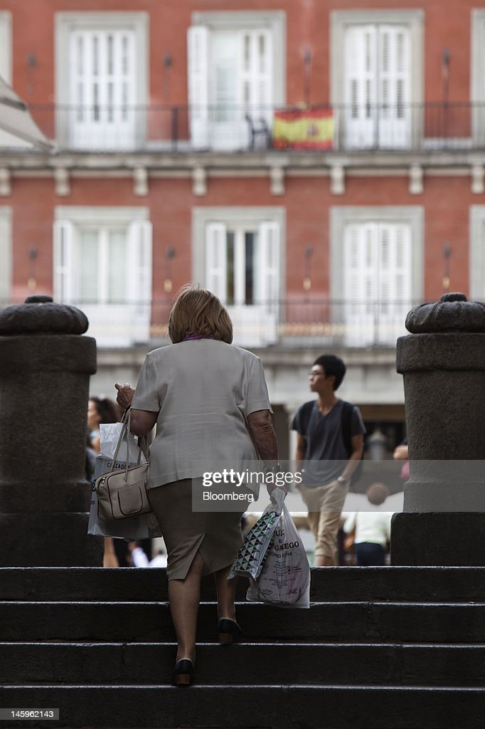 A pedestrian carries her shopping up a flight of steps in Madrid, Spain, on Friday, June 8, 2012. Spain is poised to become the fourth of the 17 euro-area countries to require emergency assistance as the currency bloc's finance chiefs plan weekend talks on a potential aid request to shore up the nation's lenders. Photographer: Angel Navarrete/Bloomberg via Getty Images