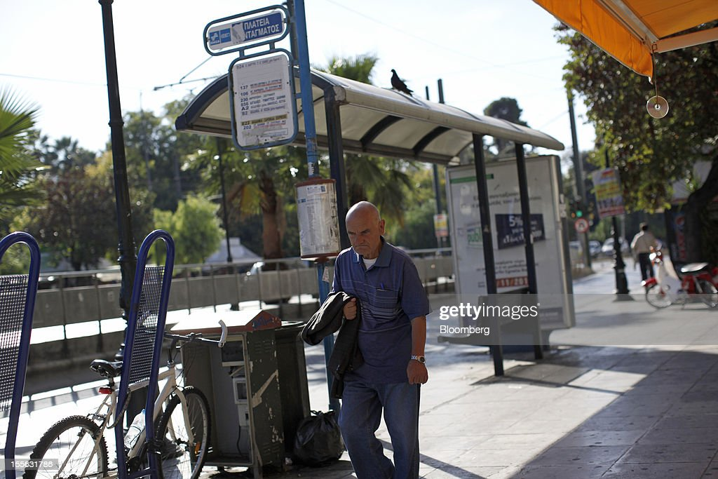 A pedestrian carries his coat along a sidewalk past an empty bus stop at the start of a general strike in central Athens, Greece, on Tuesday, Nov. 6, 2012. Greece headed for a cliffhanger vote on austerity measures needed to keep the bailout on track as a 48-hour general strike began and European officials squabbled over the timing of a deal to unlock rescue funds. Photographer: Kostas Tsironis/Bloomberg via Getty Images